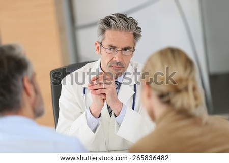 Doctor meeting couple in hospital office - stock photo