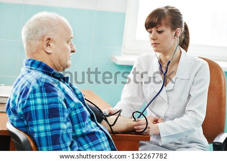 doctor nurse measuring blood pressure of patient by phonendoscope in clinic hospital - stock photo