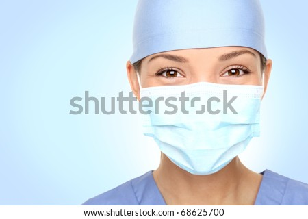 Doctor / nurse smiling behind surgeon mask. Closeup portrait of young asian caucasian woman model in blue medical scrub. - stock photo