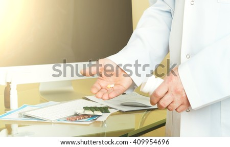 Doctor on his workplace with computer, pills, tablets, write a prescription patient data history - stock photo
