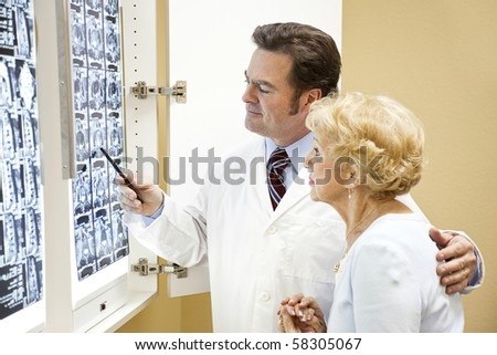 Doctor or chiropractor discussing the results of a cat scan of the spine with an elderly patient. - stock photo