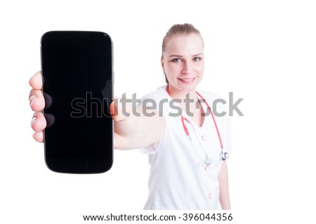 Doctor or medic female presenting blank screen mobile phone smartphone cellphone to the camera - stock photo