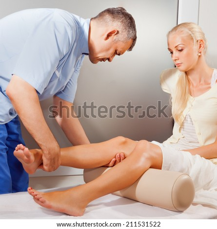 Doctor orthopedist  make examination of the knee in his office - stock photo