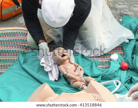 Doctor, paramedic,  The refresher training to assist childbirth newborn with a medical baby dummy in an emergency the midwife.(select focus baby dummy) - stock photo
