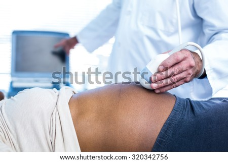 Doctor performing ultrasound on pregnant woman in hospital - stock photo
