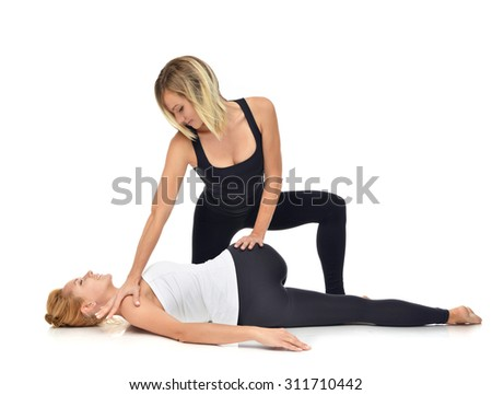 Doctor physiotherapist stretching a young sport woman isolated on a white background - stock photo