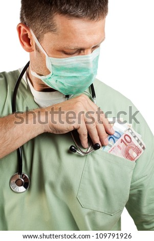 Doctor placing money in his pocket. - stock photo