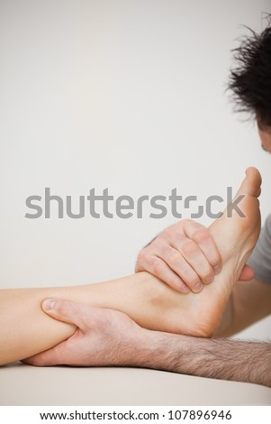Doctor pressing the side of a foot in a room - stock photo