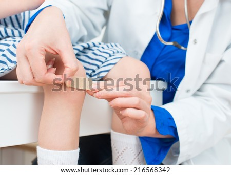 Doctor puts adhesive bandage on child knee. - stock photo