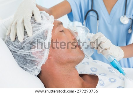 Doctor putting an oxygen mask in the hospital - stock photo