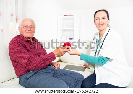 Doctor recommending an apple to his patient - stock photo