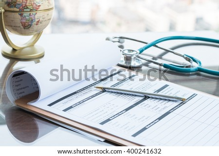 Doctor's hand working using pen writing on medical prescription blank paper form for patients with stethoscope on table/ desk: Physician taking note on empty RX paperwork in hospital/ clinic interior  - stock photo