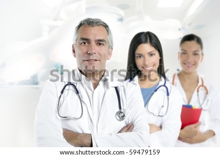 doctor senior expertise gray hair two nurses white hospital [Photo Illustration] - stock photo