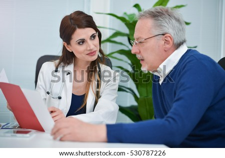 Doctor showing a medical document to a senior patient. Focus on the woman