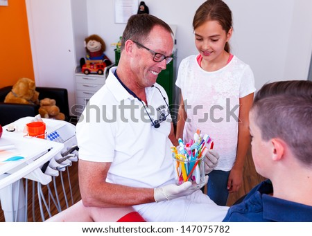 Doctor showing a teenage girl and a boy how they can care and cleaning the teeth