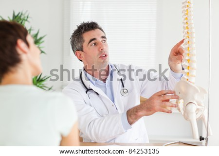 Doctor showing a woman a part of a spine in a room - stock photo
