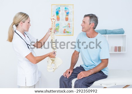 Doctor showing anatomical spine to her patient in medical office - stock photo