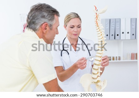 Doctor showing her patient a spine model in medical office - stock photo
