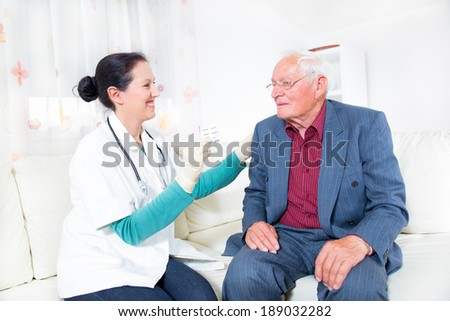 Doctor showing pills to her patient - stock photo