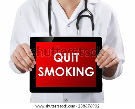 Doctor showing tablet with QUIT SMOKING text.  - stock photo