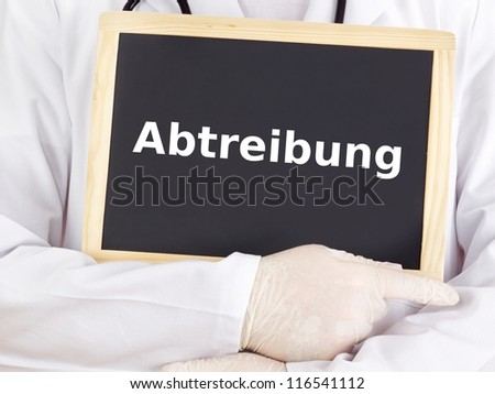 Doctor shows information on blackboard: abortion - stock photo