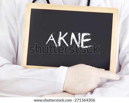 Doctor shows information on blackboard: acne in german - stock photo