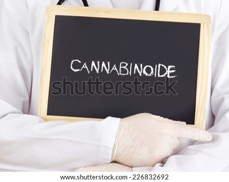 Doctor shows information on blackboard: cannabinoid in german - stock photo