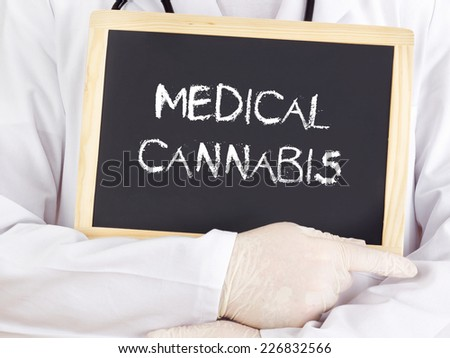 Doctor shows information on blackboard: medical cannabis - stock photo