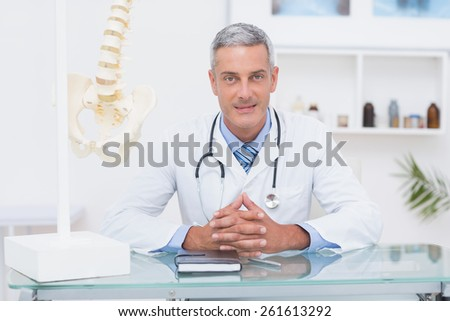 Doctor sitting at his desk smiling at camera in medical office - stock photo