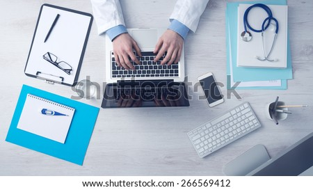 Doctor sitting at office desk and working on his laptop with medical equipment all around, top view - stock photo