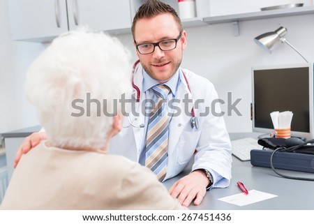 Doctor sitting with pensioner in surgery consultation hour at desk - stock photo