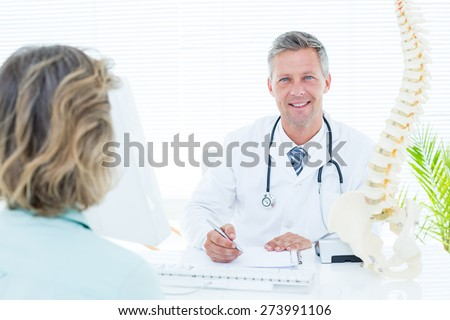 Doctor smiling at camera in medical office - stock photo