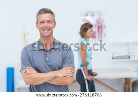 Doctor smiling at camera while his patient standing with crutch in medical office - stock photo