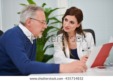 Doctor speaking to her patient while showing some documents
