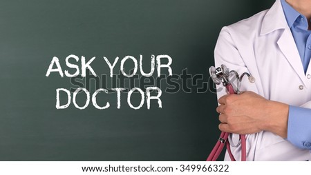 Doctor Standing front of Blackboard written ASK YOUR DOCTOR - stock photo