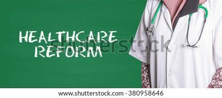 Doctor Standing front of Chalk Board written DENTIST - stock photo