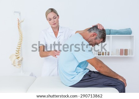 Doctor stretching a man back in medical office - stock photo