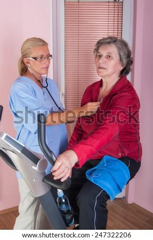Doctor supervising a senior woman - stock photo