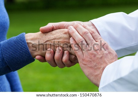 Doctor supporting an elderly woman, green background - stock photo
