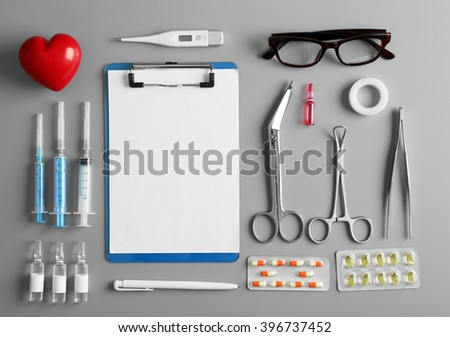 Doctor table with medical items and medicines, top view - stock photo