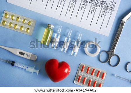 Doctor table with medical items and pills on blue background, top view