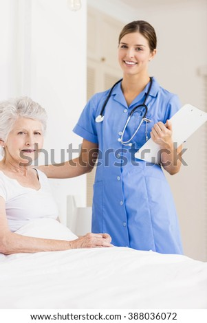 Doctor taking care of suffering senior patient at home - stock photo