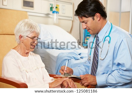 Doctor Taking Notes From Senior Female Patient Seated In Chair By Hospital Bed - stock photo