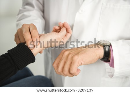 Doctor taking patient's pulse. - stock photo
