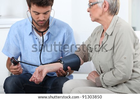 Doctor taking the blood pressure of a patient - stock photo