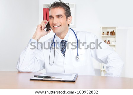 Doctor talking on mobile phone, sitting at desk . - stock photo