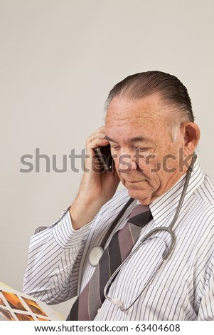 Doctor talking on phone and looking at pictures of colon exam. - stock photo