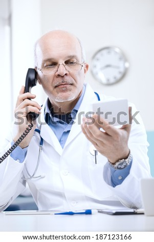 Doctor talking on the phone and looking at medicine's box.