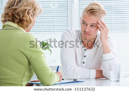 doctor talking to her male patient at office - stock photo