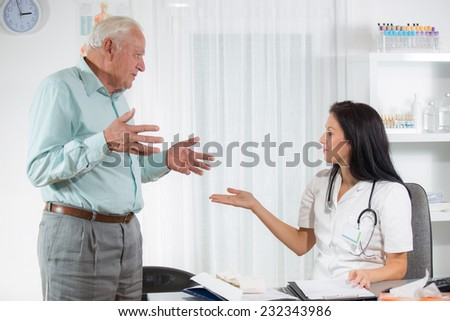 Doctor talking to her male senior patient at office, selective focus - stock photo